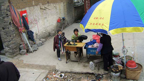 街頭で衣服を仕立てる女(懐かしい足踏式)